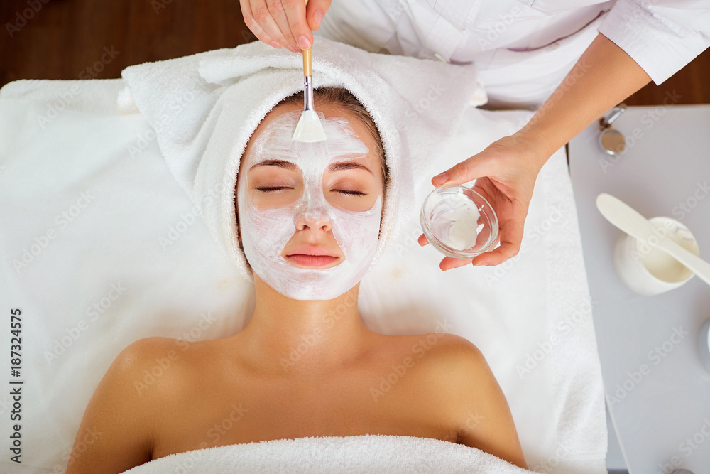 Fototapeta Woman in mask on face in spa beauty salon.