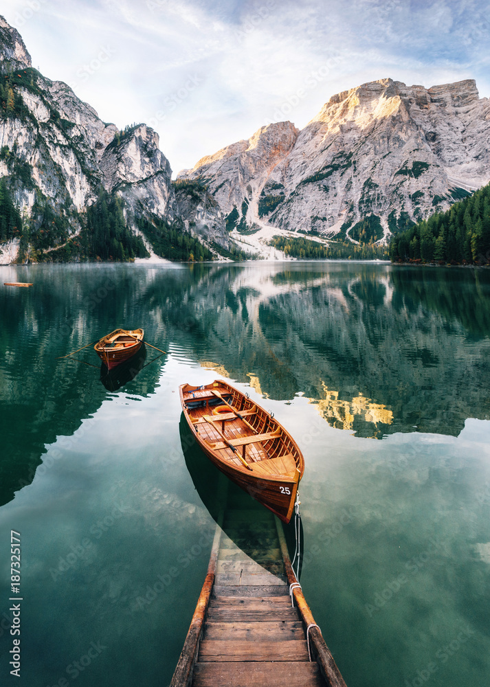 Fototapeta Boats and slip construction in Braies lake with crystal water in background of Seekofel mountain in Dolomites in morning, Italy Pragser Wildsee