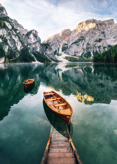 Obraz na Plexi Boats and slip construction in Braies lake with crystal water in background of Seekofel mountain in Dolomites in morning, Italy Pragser Wildsee
