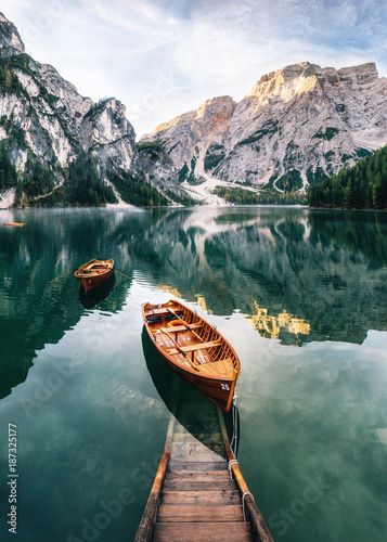 Poster Bergen Boats and slip construction in Braies lake with crystal water in background of Seekofel mountain in Dolomites in morning, Italy Pragser Wildsee