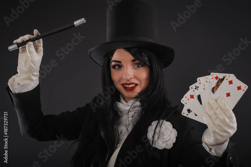 Female magician in performer suit with magic wand and playing cards