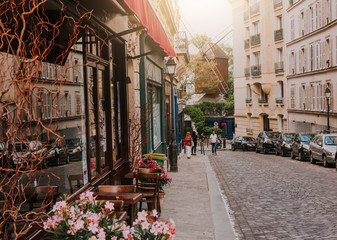 Fototapeta Cozy street with tables of cafe and old mill in quarter Montmartre in Paris, France