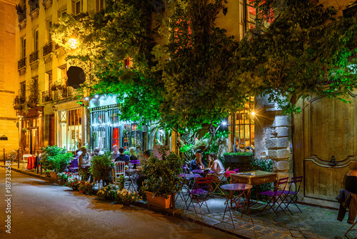 Cozy street with tables of cafe in Paris at night, France Poster