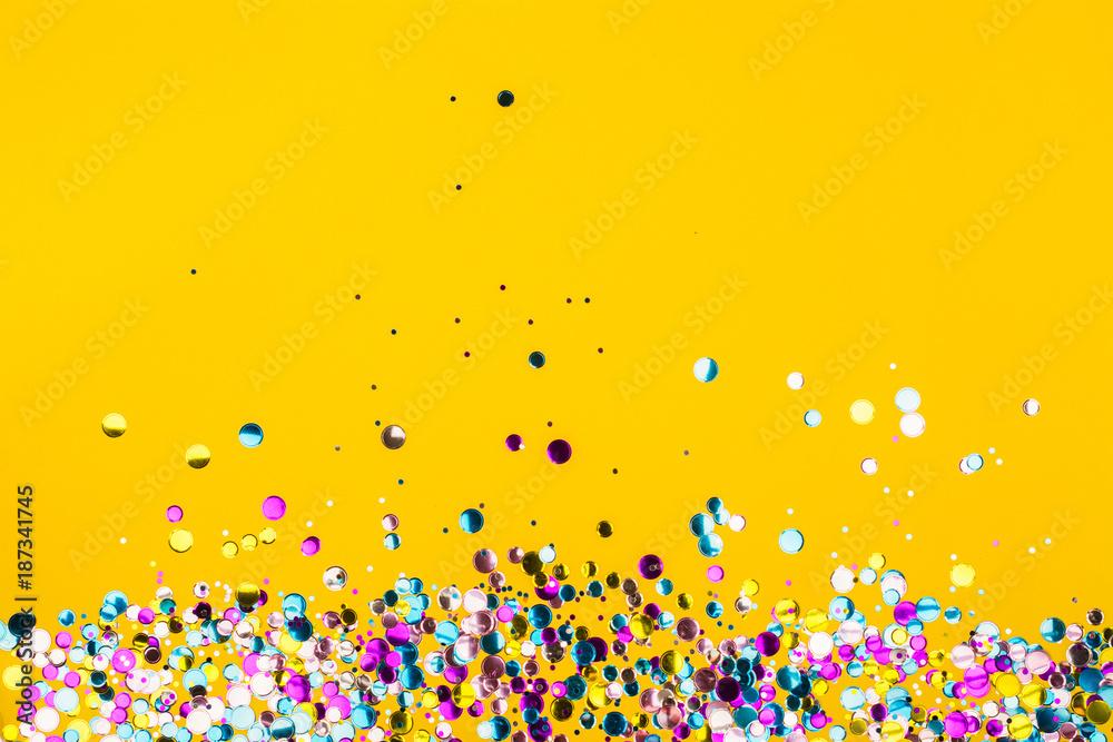 Fototapeta Colorful confetti on yellow background