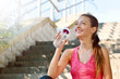 Sporty woman drinking water after jogging