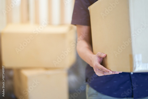 Obraz close up man hand carrying big box for moving from old home to new home , relocation concept - fototapety do salonu