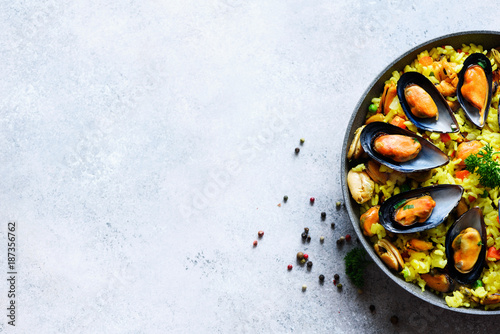 Photo Traditional spanish seafood paella in pan rice, peas, shrimps, mussels, squid on light grey concrete background