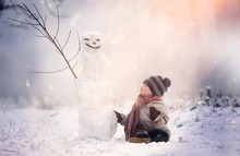 Young Boy Sitting Near Snowman...