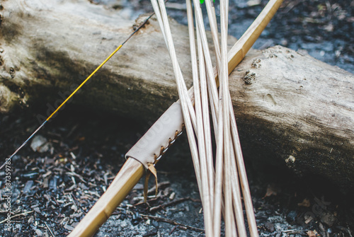 Fotografía  Traditional bow and wooden arrows laying on the log in the forest