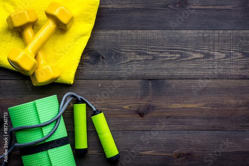 Fototapeta Fitness equipment. Dumbbells, mat, jumping rope on dark wooden background top view copyspace obraz na płótnie