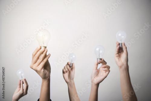 Fototapeta hand holding light bulb, concept teamwork ideas with innovation and creativity. obraz na płótnie