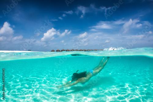 Foto op Canvas Onder water Attraktive Frau im Bikini taucht in klaren, tropischen Gewässern; Sommerurlaubs Konzept