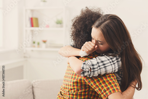 Woman hugging her depressed friend at home Canvas Print