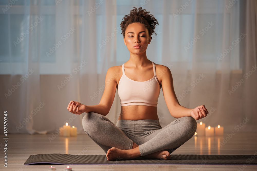 Fototapeta Just breathe and relax. Portrait of serene young woman enjoying meditation in apartment. Her eyes are closed with pleasure