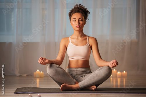 Just breathe and relax. Portrait of serene young woman enjoying meditation in apartment. Her eyes are closed with pleasure