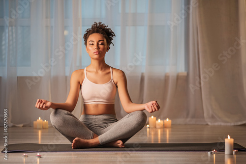 Full length portrait of peaceful african girl meditating in cozy room. Candles are near her on floor
