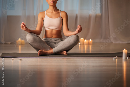 Low angle of relaxed young woman doing yoga exercise for total relaxation. She is sitting on mat in lotus position and making hands in special posture. Copy space