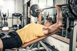 Man lies on the gym bench and does barbell exercises