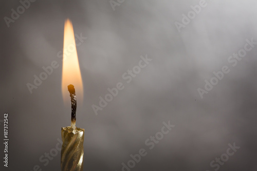 Fotografie, Obraz  Burning Gold Candle on a Silver Background
