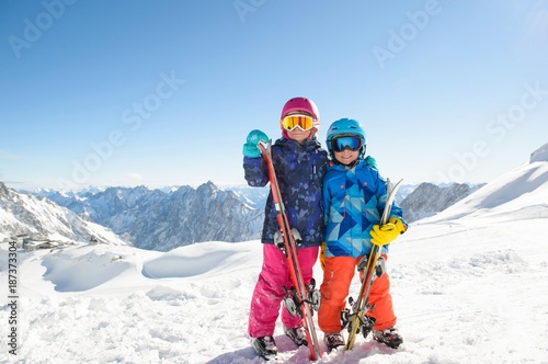 Smiling children  enjoying winter vacations in mountains . Ski, Sun, Snow und fun.