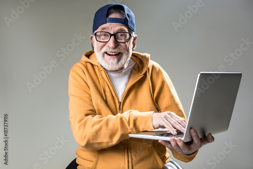 Obraz Waist up portrait of trendy pensioner enjoying the use of new laptop. He is looking at camera with big smile. Isolated on grey background - fototapety do salonu