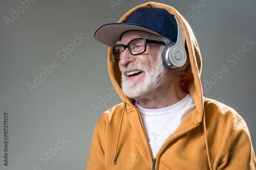 Contemporary bearded gaffer spending time with favorite song. He is looking aside and laughing. Copy space in left side. Isolated on grey background