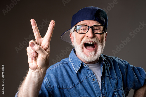 Fotografia  Portrait of cheery greybeard in cap showing peace sign and laughing