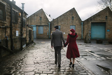 Couple Wearing Vintage Clothes Walk Towards A Disused Industrial Building.