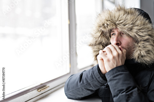 Man With Warm Clothing Feeling The Cold Inside House close to a window Tablou Canvas