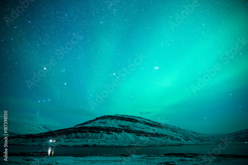 Foto op Canvas Groene koraal Northern lights over the snowy mountains and stars sky at winter