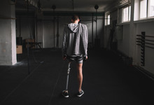 Rear View Of Man With Prosthetic Leg Standing In Gym