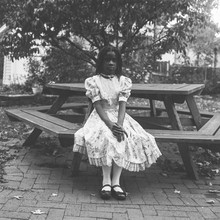 Black Girl In A Victorian Dress Sitting At A Table