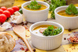 Homemade sausage soup with parsley in white ramekin bowls