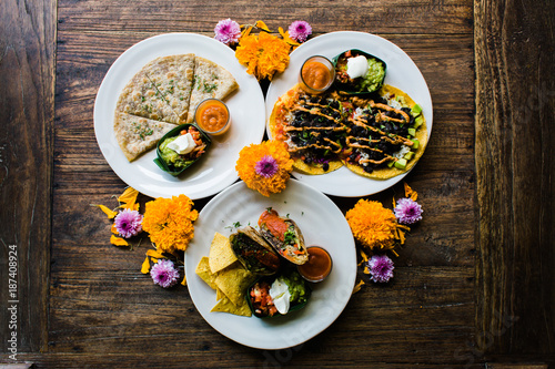 Overhead view of Mexican food decorated with flowers on table