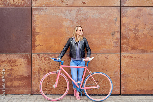 Woman with vintage fixed bike in the street.