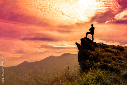The man stands on a cliff top and orange