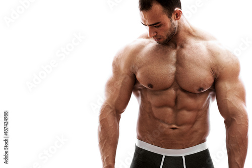 Fotografie, Obraz  Strong muscular bodybuilder man with perfect trained body standing against white background and looking down