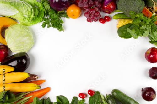 Flat lay of vegetable and fruits with empty space of white background on middle, Top view. Vegetarian, diet food, grocery fresh produce and healthy eating concept. © piyaset