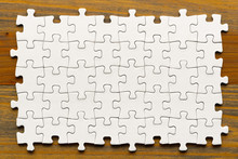 Puzzle Background. White Pieces On Wooden Table. Partially Completed Box Shaped Puzzle Pieces.