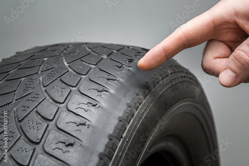 Man's hand finger pointing to the old, damaged and worn black tire tread. Change time. Tire tread problems and solutions concept. © fotoduets