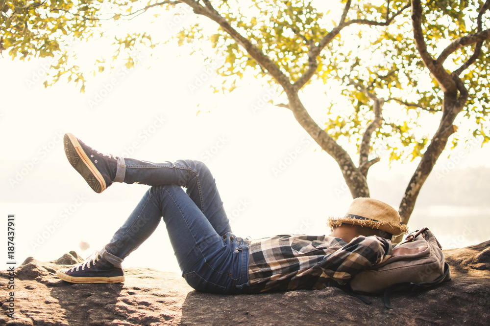 Fototapeta Boy backpacker sleeping on the rock in nature , Relax time on holiday concept travel,selective and soft focus,tone of hipster style