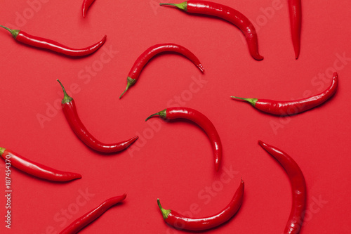 Poster Hot chili peppers Red chili peppers arranged on a bright red background