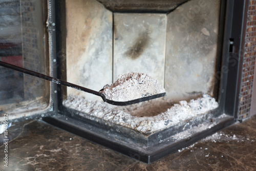Photo Man cleaning fireplace from ashes