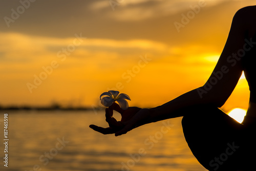 Close up Silhouette hands. Woman do yoga outdoor. Woman exercising vital and meditation for fitness lifestyle club at the sunset beach background. Healthy Concept.