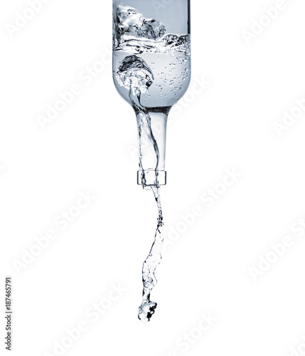 motion shot of water pouring from glass bottle isolated on white Canvas Print