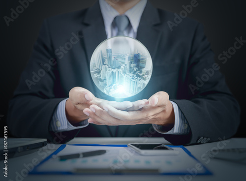 businessman hand hold crystal ball with building inside Canvas Print