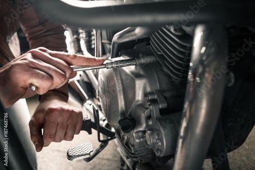 Fototapeta premium Zamyka up mężczyzna ręki naprawianie motocykl