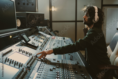 Photo  side view of concentrated sound producer working at studio