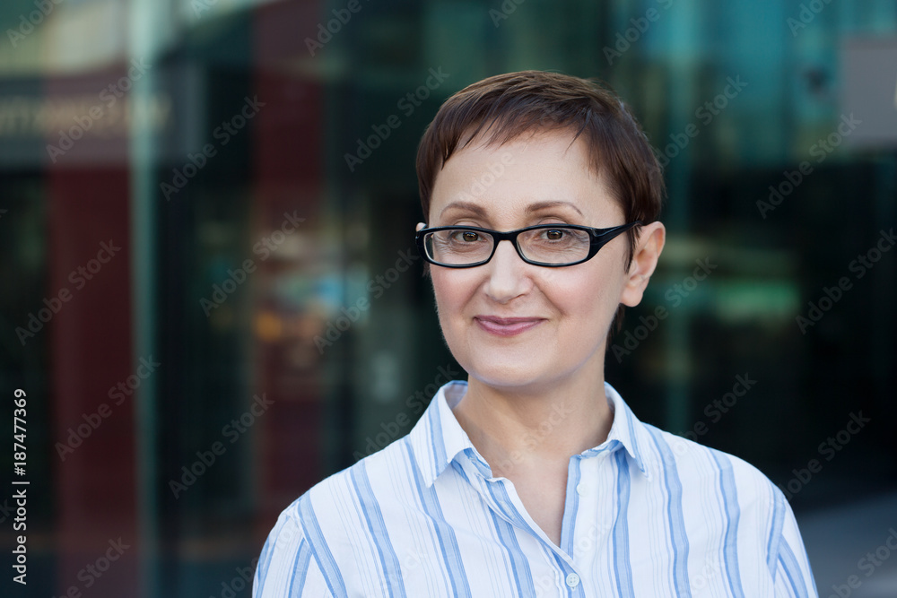 Fototapeta Older business woman headshot. Close-up portrait of executive, teacher, principal, CEO. Confident and successful middle aged woman 40 50 years old wearing glasses and shirt and smiling