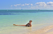 Long haired young woman in bikini in water on tropical beach. Girl young lying on the beach sand happy in summer vacation. Cuba. Caya Coco